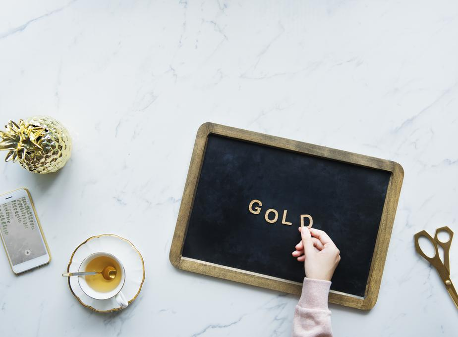 flatlay of a model spelling gold on a blackboard Or : Les vraies raisons de la nouvelle ruée vers le métal jaune ?